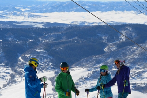 Four skiers under the gondola at Steamboat Resort.